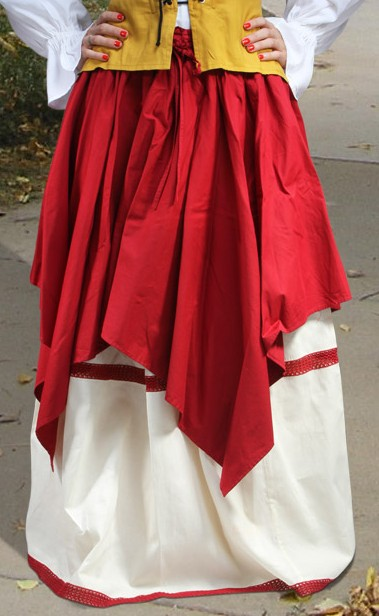 Two-layer skirt has Kerchief Skirt with assymetrical hem, over a full skit with braid trim.